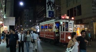 خیابان اصلی دور میدان تقسیم با تراموای قرمز رنگ در وسط